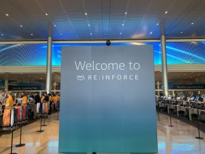 """A wide angle shot of the conference registration desk for AWS re:Inforce with an endcap wall in a slight teal blue saying, """"Welcome to AWS re:Inforce"""""""
